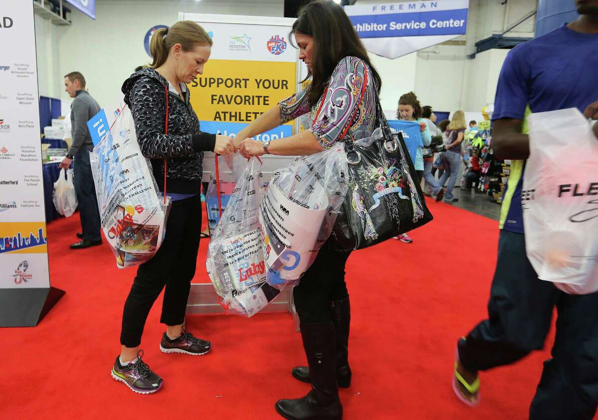 Jamie Beller and Melissa Lyles of Katy, Texas pick up support signs for running packets at the Memorial Hermann IRONMAN Sports Medicine Institute EXPO at George R. Brown Convention Center on Friday, Jan. 15, 2016, in Houston. The two were supporting Vanessa's Big Heart Foundation.