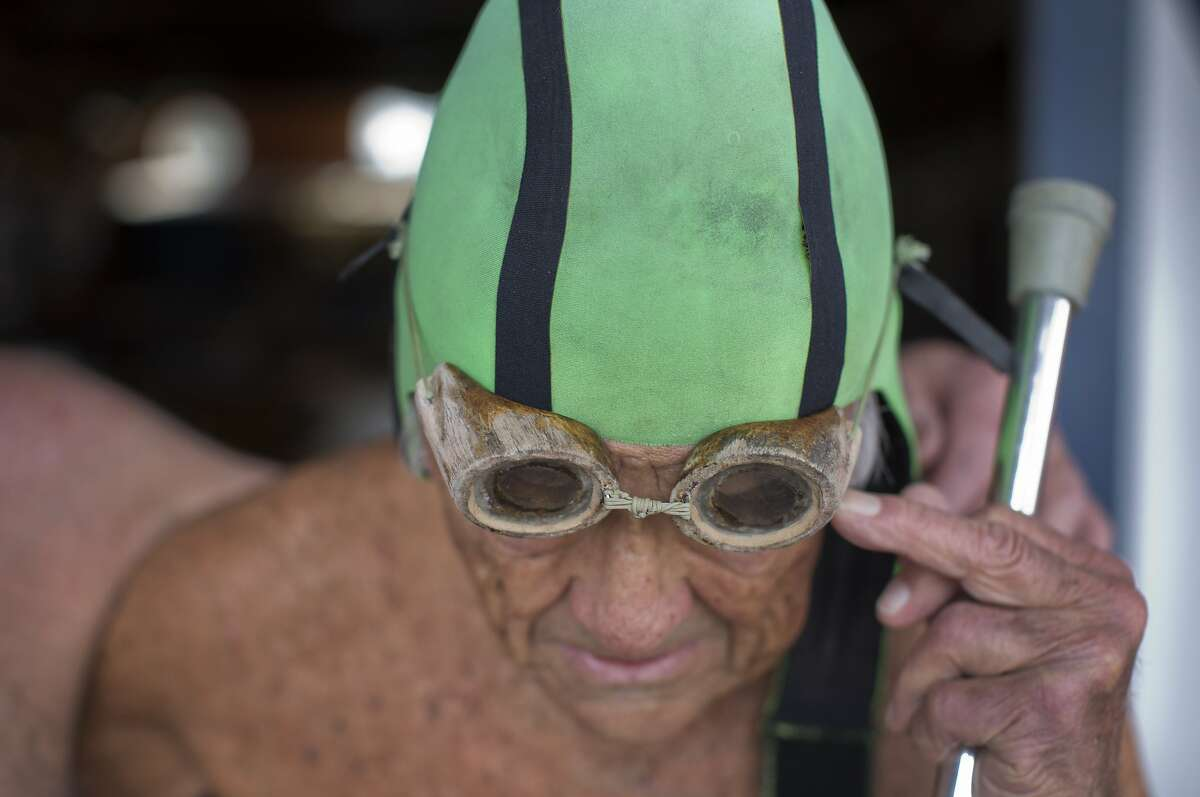 Walt Schneebeli adjusts his goggles before a swim at the Dolphin Club. Schneebeli has been wearing the same goggles since the 1950's. He still swims in the bay water several times a week with a group that calls themselves 'the old goats.'