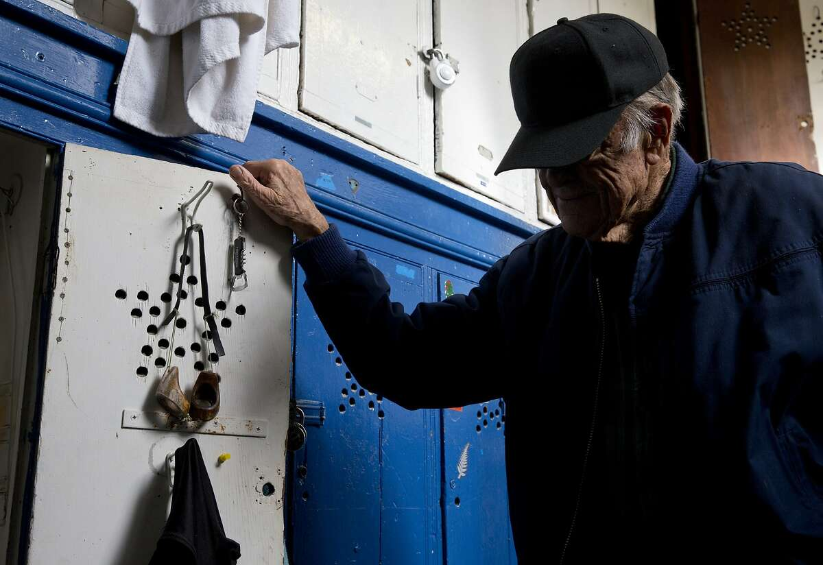 Walt Schneebeli, 90, peers inside his locker at the Dolphin Club where he's been a member since 1948. He's worn the same wood and glass goggles from Hawaii since the 1950's.