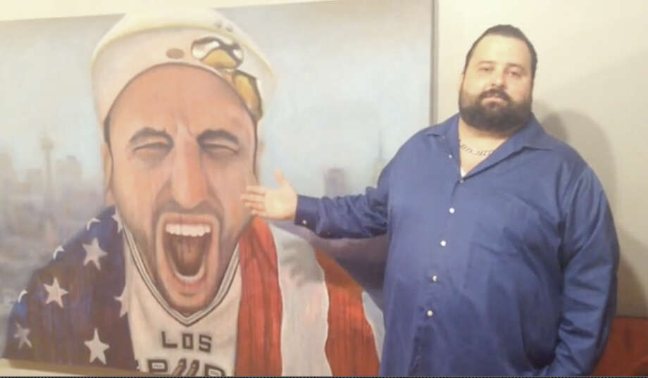 San Antonio artist Victor De La Fuente shows off his painting of Spurs star Manu Ginobili. Photo: Nick Moyle /San Antonio Express-News