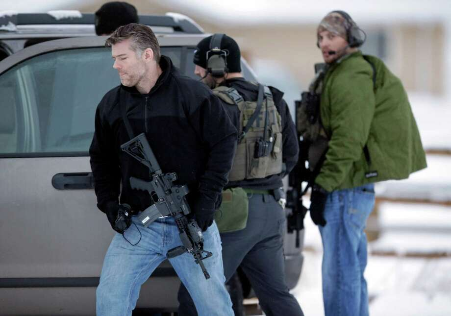 Members of the FBI stand guard at the Burns Municipal Airport in Burns, Ore. A small, armed group has been occupying a remote national wildlife refuge in Oregon to protest federal land use policies. A reader decries the lack of aciton against the group. Photo: Rick Bowmer /Associated Press / AP