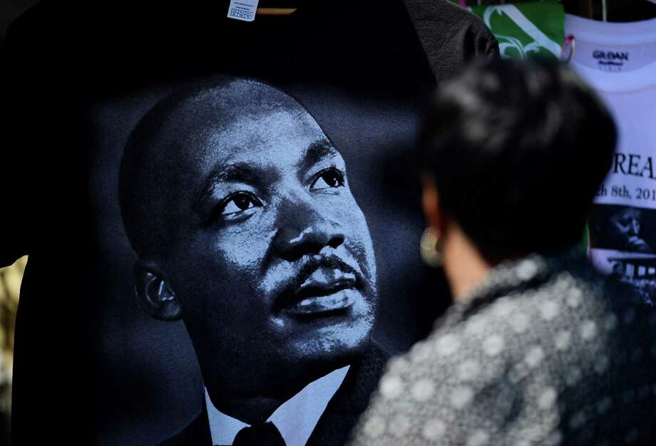 A woman looks at t-shirt with the likeness of Martin Luther King Jr. If we are to realize a deeper understanding of King's theology and political philosophy, we need to broaden our understanding of democracy by conceptualizing it holistically. Photo: Bill Frakes /Associated Press / FR171302 AP