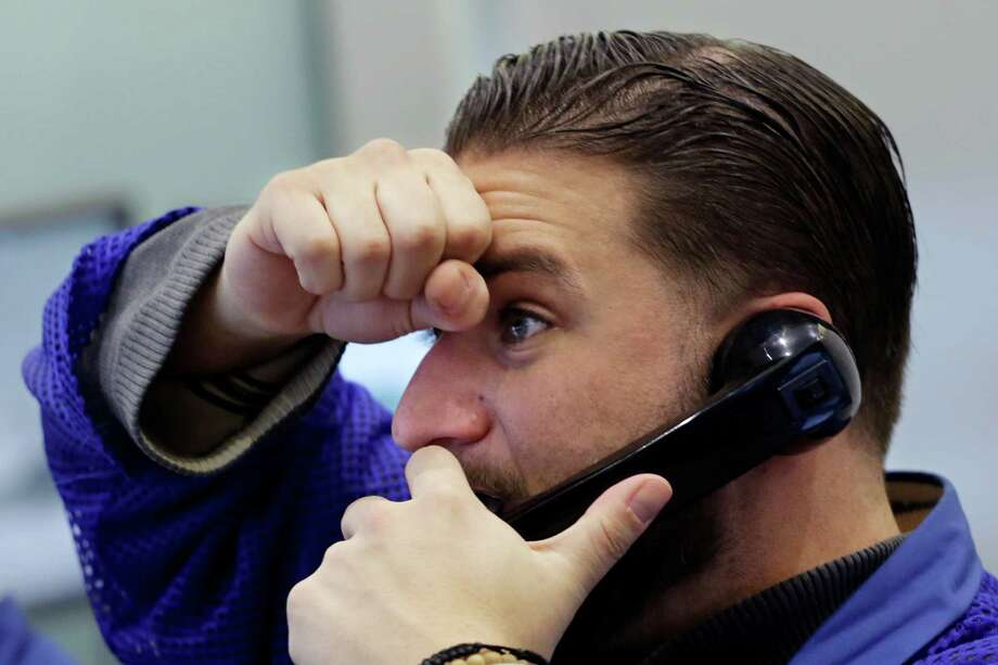 Trader Chris Dattolo watches prices on stock options Friday at the New York Stock Exchange. If you look at your 401(k) mutual funds or stocks or funds in your IRA, it's not going to be pretty. Photo: Mark Lennihan /Associated Press / AP