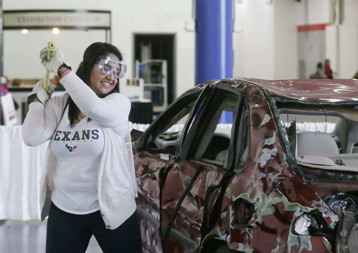 Adilene Flores swings a sledgehammer at a car as part of a Houston Texans promotion at the Bridal Extravaganza Show at the George R. Brown Convention Center Saturday, Jan. 9, 2016, in Houston. ( Jon Shapley / Houston Chronicle )