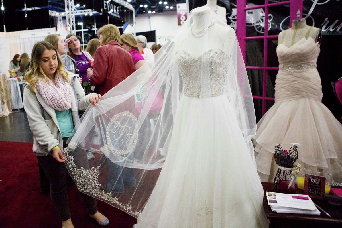 Kimberly Pingenot, 19, of San Antonio checks out a veil with an embroidered monogram at the Princess Bridal booth during the Bridal Extravaganza Show. Industry experts say millennials are prioritizing their budgets.
