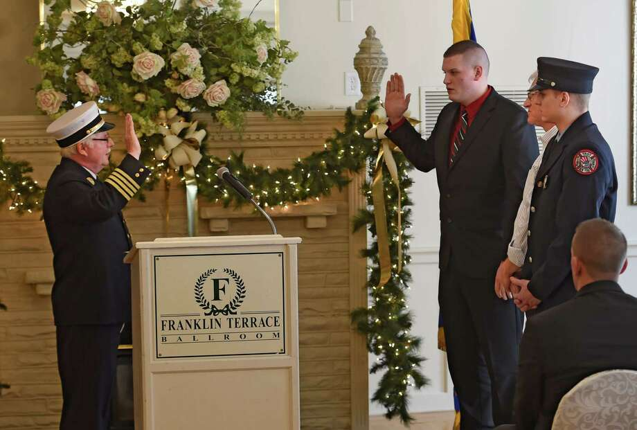 Assistant Chief James Hughs swears in a second generation firefighter Jordan Baldwin, third from right, as his uncle retired Battalion Chief Ray Davis, second from right and his brother Tyler Baldwin watch this afternoon at the Franklin Terrace Jan. 15, 2015 in Troy, N.Y.       (Skip Dickstein/Times Union) Photo: SKIP DICKSTEIN / 10034988A