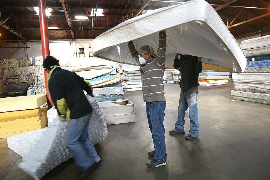 Left to right--Employees Miguel Mendez, Jonathon Diaz, and Mauricio Hacho separate and stack mattress material at Oakland's DR3 Mattress Recycling Center in Oakland, California, on Friday,  January 15, 2016.  A new state law allows residents to recycle mattresses for free. Photo: Liz Hafalia, The Chronicle