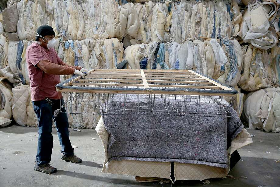 Employees Nery Garcia works on separating materials from a mattress at Oakland's DR3 Mattress Recycling Center in Oakland, California, on Friday,  January 15, 2016.  A new state law allows residents to recycle mattresses for free. Photo: Liz Hafalia, The Chronicle
