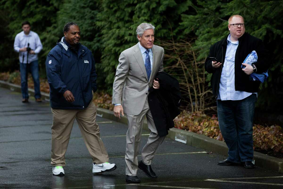 Seahawks head coach Pete Carroll walks back into the Virginia Mason Athletic Center before hopping on the bus to go to the team's game against the Carolina Panthers, photographed in Renton on Friday, Jan. 15, 2016.