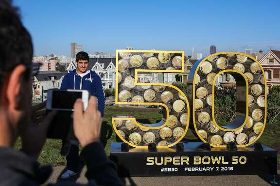 "Paulo Kirschner, a tourist from Brazil gets his photo taken next to a six-foot ""50"" sculpture, which is one of ten installed around the city to celebrate the start of the Super Bowl, at Alamo Square Park, in San Francisco, California on Friday, January 15, 2016."