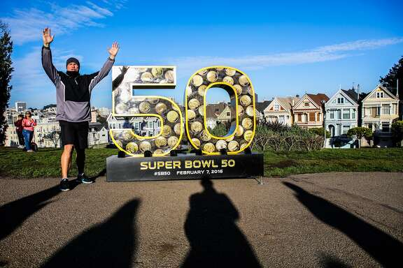 "David Winford of Maraga yells touchdown as his wife Alla Winford (not pictured) takes a photo of him next to a large sculpture of the number ""50"", which is one of ten sculptures installed around the city to celebrate the start of the Super Bowl, at Alamo Square Park, in San Francisco, California on Friday, January 15, 2016."