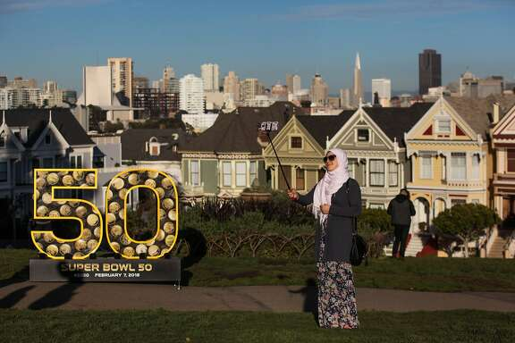 "Nihed Kassab, a tourist from Tunisia takes a selfie with a six-foot number ""50"" sculpture, which was installed as part of the Super Bowl celebration, at Alamo Square Park, in San Francisco, California on Friday, January 15, 2016."