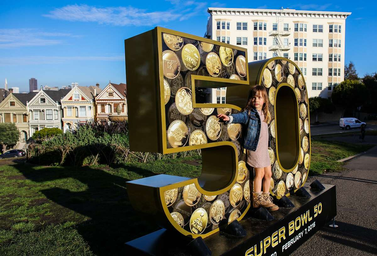 """Vesper Shreve, 5 walks across a six-foot sculpture of the number """"50"""", which is one of ten that have been installed across the city for the Super Bowl, in Alamo Square Park, in San Francisco, California on Friday, January 15, 2016."""