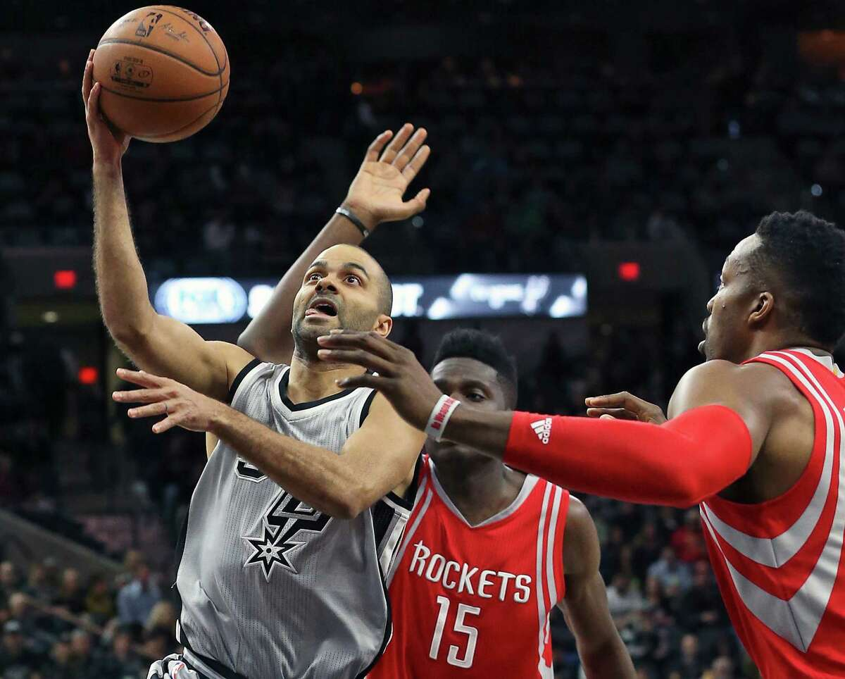 Tony Parker puts up a shot against Dwight Howard (right) after beating Clint Cappella inside as the Spurs host the Rockets at the AT&T Center on January 2, 2016.