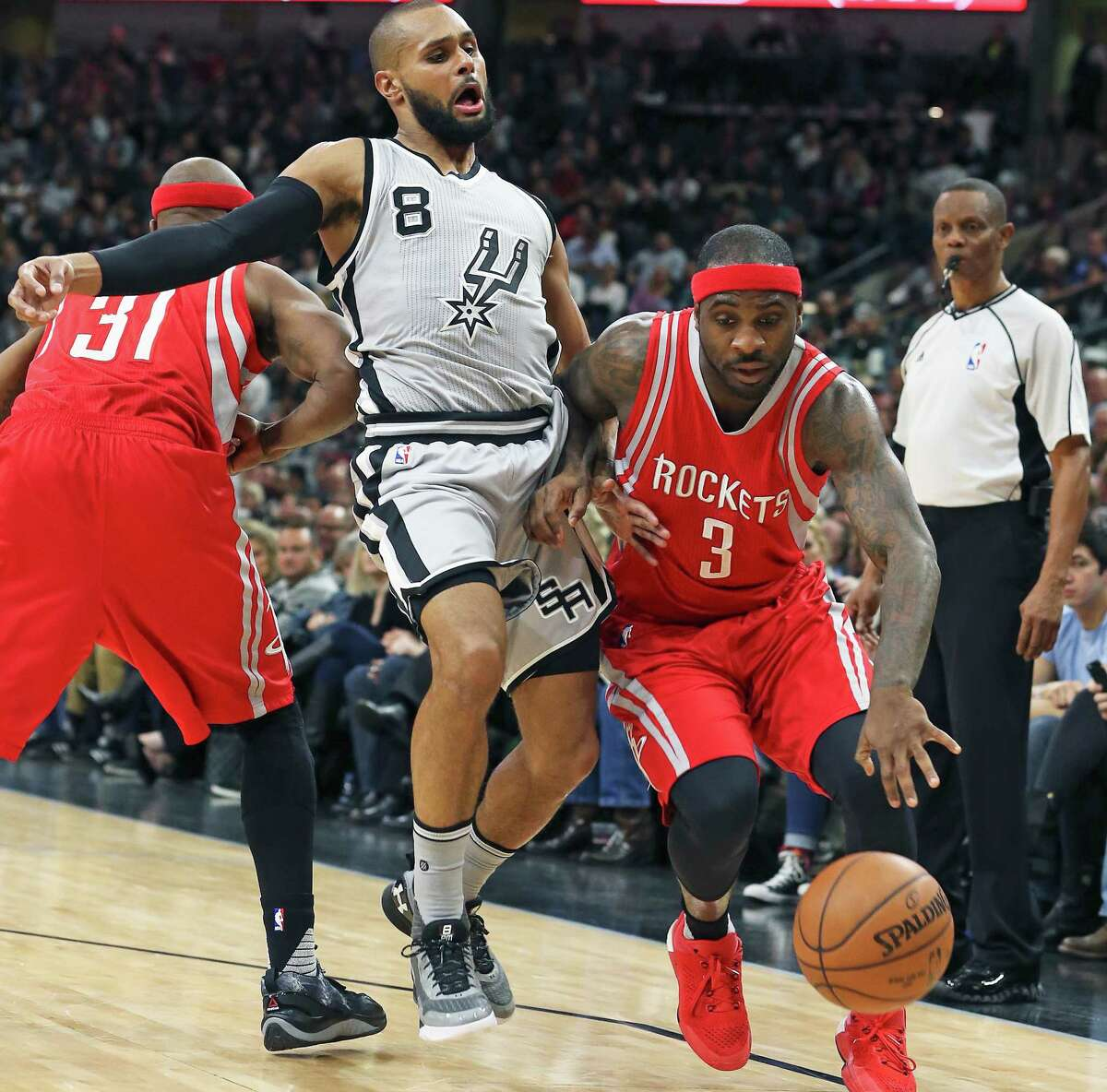 Patty Mills is caught in a screen byJason Terry as Ty Lawson tries to get to the lane as the Spurs host the Rockets at the AT&T Center on January 2, 2016.