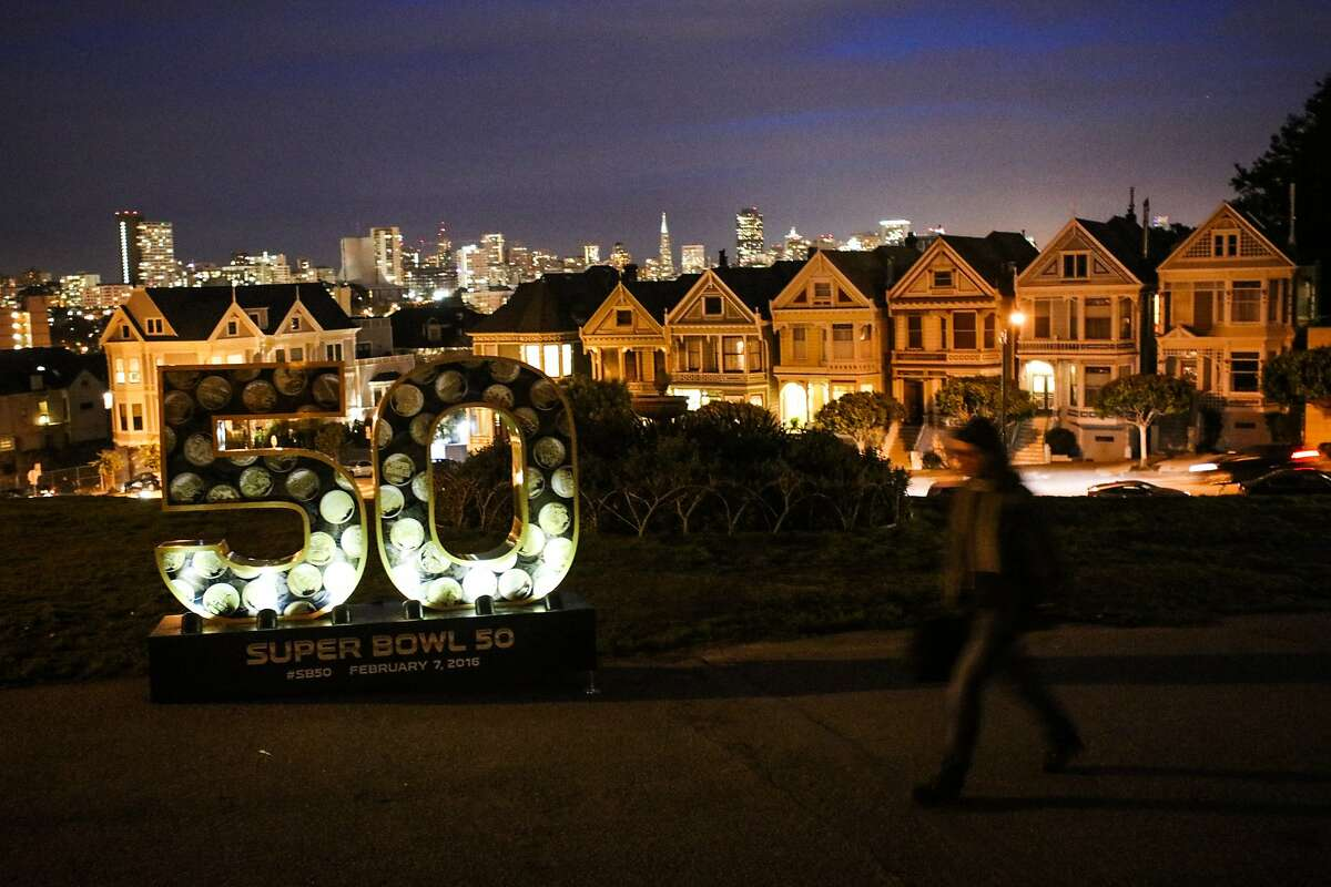 """A woman walks past a six-foot sculpture of the number """"50"""", which is one of ten that have been installed across the city for the Super Bowl, in Alamo Square Park, in San Francisco, California on Friday, January 15, 2016."""