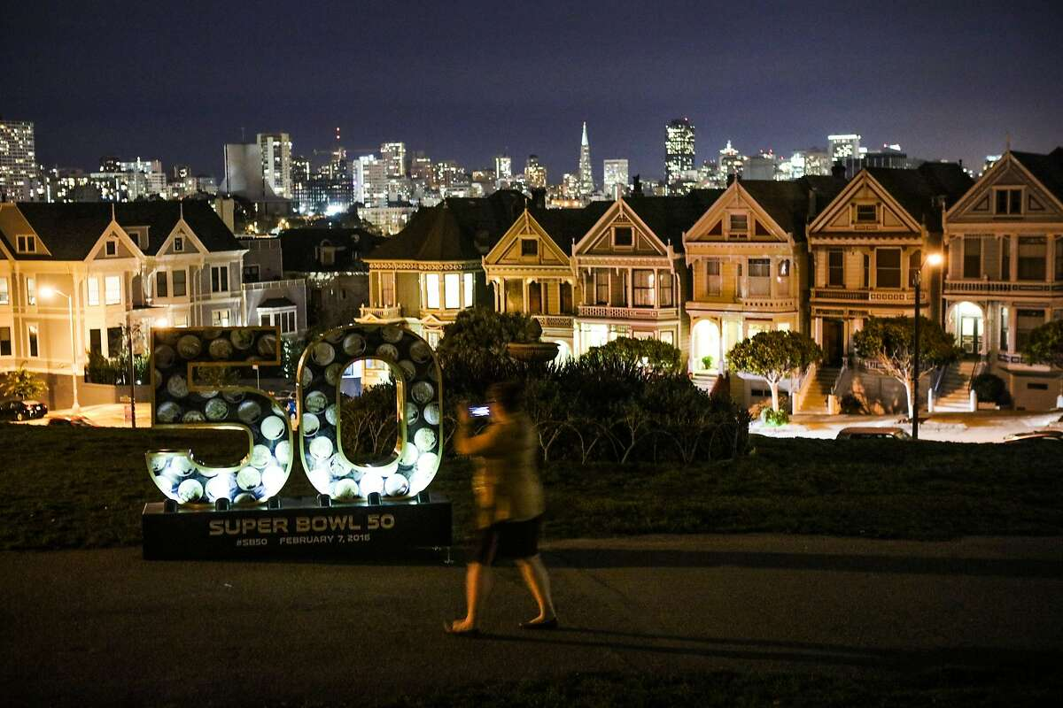 Tali Braunstein stops on her way through Alamo Square Park to take a photo of a large sculpture of the number