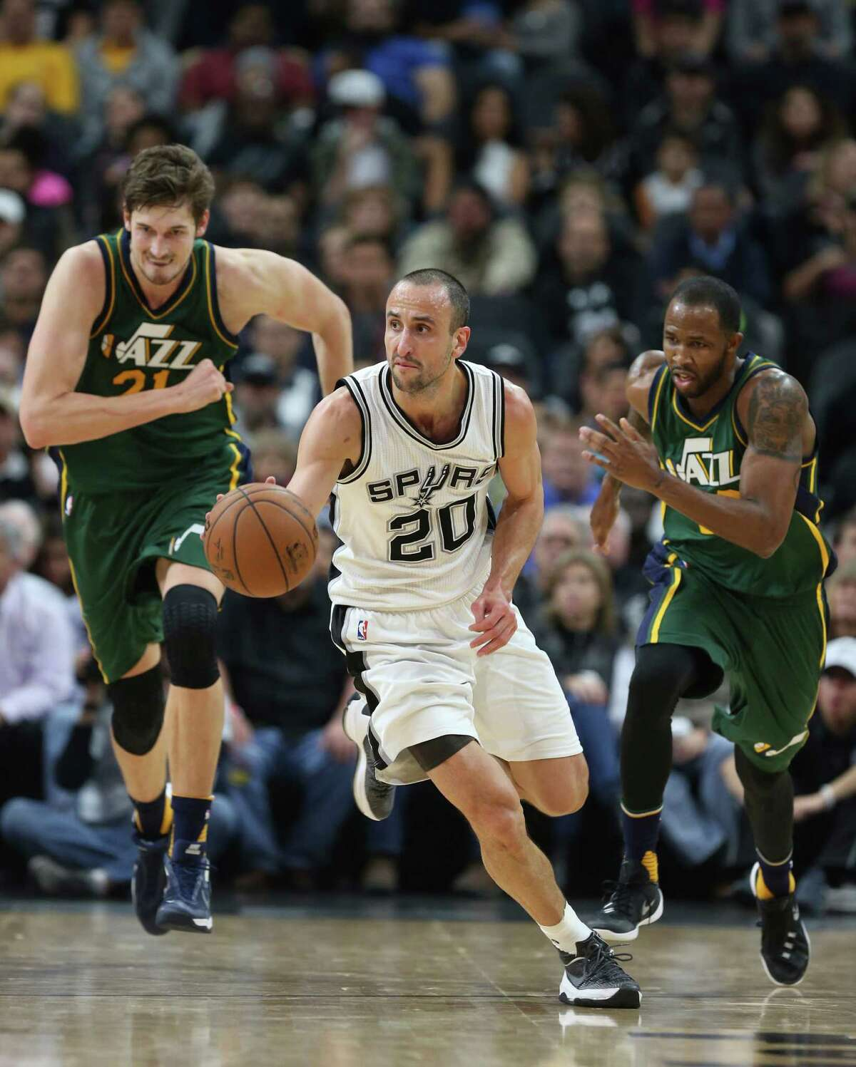 San Antonio Spurs' Manu Ginobili drives the ball as Utah Jazz' Tibor Pleiss, left, and Chris Johnson try to catch up during the second half at the AT&T Center, Wednesday, Jan. 6, 2016. The Spurs won, 123-98.