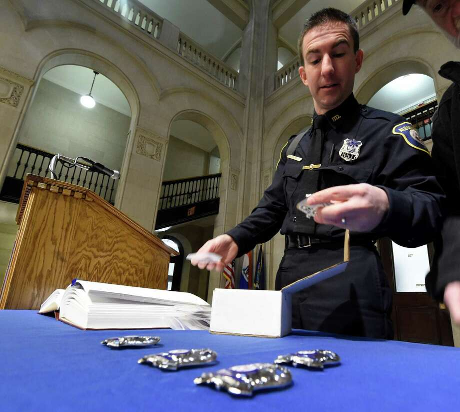 Albany Police Public Information Officer Steve Smith lays out the badges for the 10 new members of the department before the swearing in ceremony held at City Hall Friday morning Jan. 15, 2015 in Albany, N.Y.       (Skip Dickstein/Times Union) Photo: SKIP DICKSTEIN