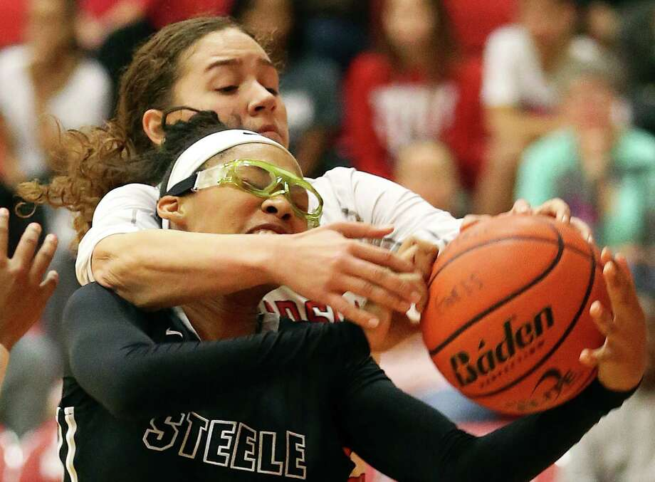Steele's Kavin Johnson struggles to control the ball under the hoop with Kyra White of Judson reaching over her back to contest on Jan. 15, 2016. Photo: Tom Reel /San Antonio Express-News / 2016 SAN ANTONIO EXPRESS-NEWS