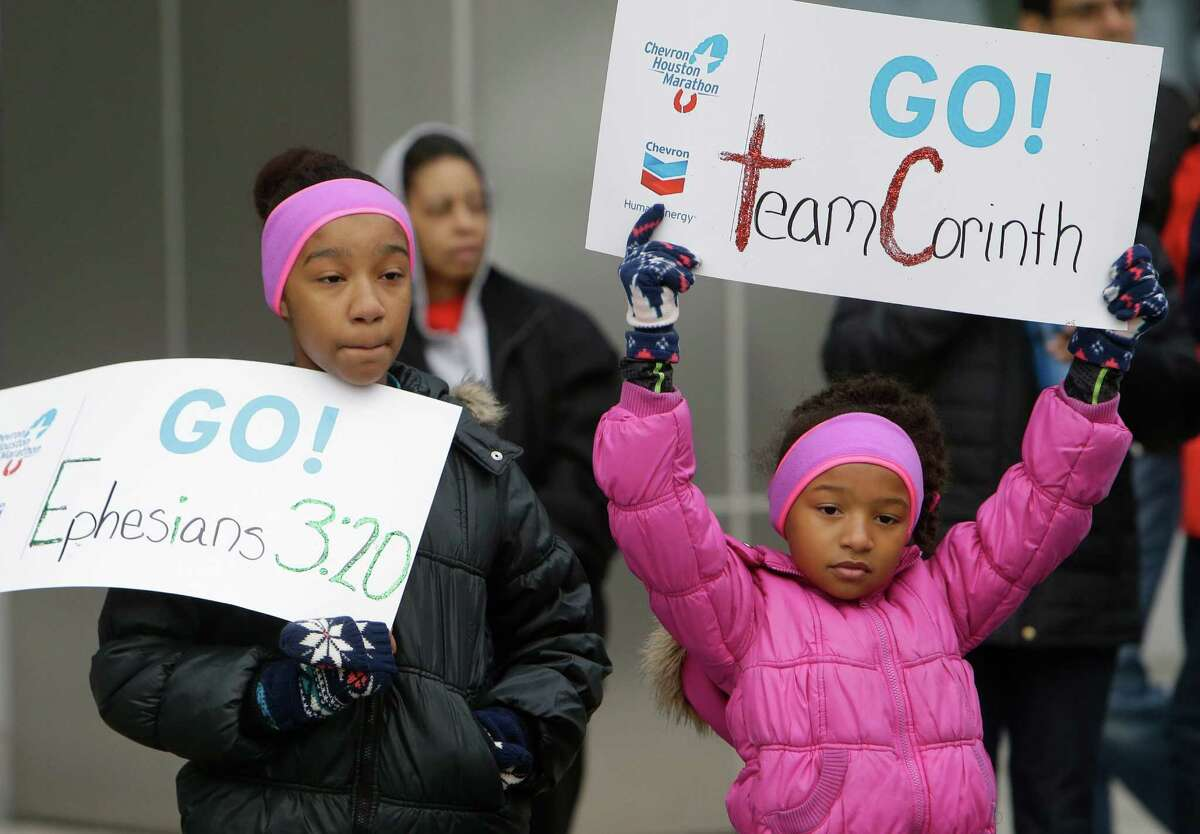 Jordan Marson, 12, left, and her sister, Jensen, 8, brave the cold weather to support church members of Mount Corinth participating in the ABB 5K in downtown Houston Saturday, Jan. 16, 2016.