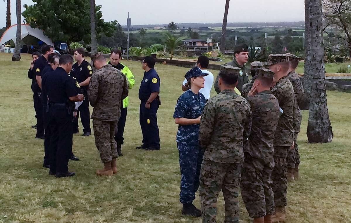 Military officials and Honolulu Police Department officers talk at a beach park where search and rescue officials are meeting in Haleiwa, Hawaii, Friday, Jan. 15, 2016, after two U.S. Marine helicopters carrying 12 crew members collided off the Hawaiian island of Oahu during a nighttime training mission. Rescuers were searching a debris field in choppy waters Friday, military officials said. (AP Photo/Audrey McAvoy)