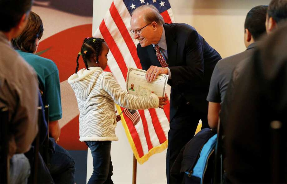 Bexar County Judge Nelson Wolff (right) hands five-and-a-half-year-old Aliya Omar her Certificate of Citizenship as the DoSeum hosts a ceremony in cooperation with U.S. Citizenship and Immigration Services on Saturday, Jan. 16, 2016. 52 children from 24 countries qualified for a Certificate of Citizenship as flags were waved and as guests watched a video message from President Barack Obama. Locally, Bexar County Judge Nelson Wolff spoke at the event and presented the new Americans with their certificates. Immigration services officials said they plan on holding similar events up to four times a year. The local immigration office serves 78 counties in South Central Texas. (Kin Man Hui/San Antonio Express-News) Photo: Kin Man Hui, Staff / San Antonio Express-News / ©2016 San Antonio Express-News