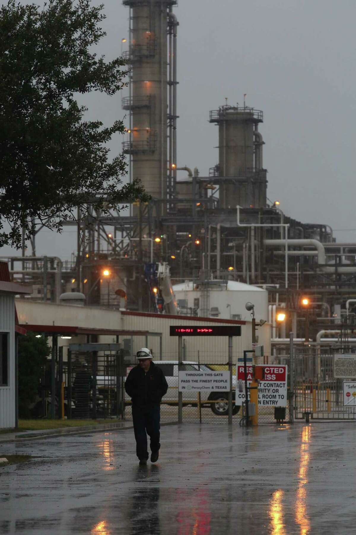 A man walks by the gate of a PeroxyChem plant in the 12000 block of Bay Area Blvd, in the Bayport complex, Saturday Jan. 16, 2016, in Pasadena. One person was killed and three were injured in a chemical explosion or leak, according to authorities.