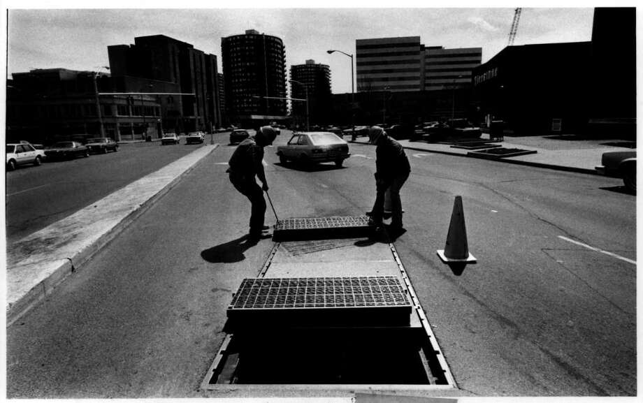 April 4, 1985: Northeast Utilities workers replace a grate on Washington Boulevard after a transformer blew out rocking buildings nearby. Photo: File Photo / Stamford Advocate File Photo