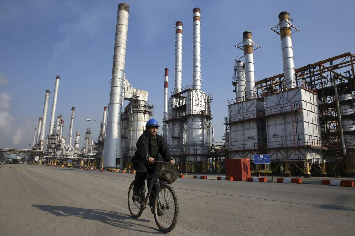 An Iranian oil worker rides his bicycle at the Tehran's oil refinery south of the capital Tehran. Iran put out an additional 220,000 barrels a day last month, not enough to overwhelm the overseas market.