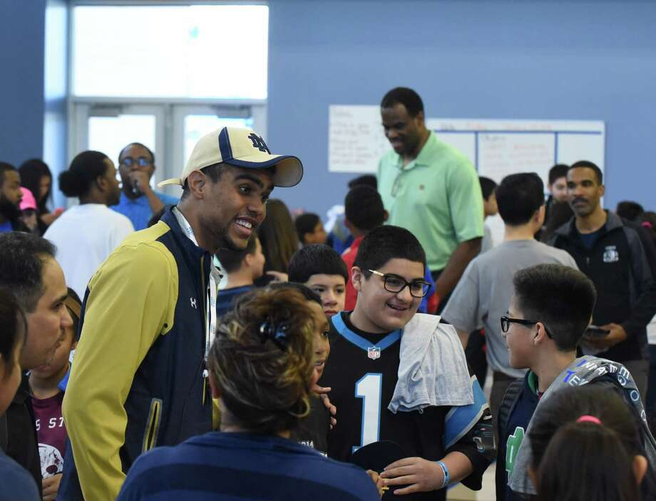 Notre Dame football wide receiver Corey Robinson and his father, former San Antonio Spurs player David Robinson, in background, converse with students at IDEA Carver on Saturday, Jan. 16, 2016, where they and college student athletes encouraged students and distributed T-shirts with logos of various universities through the One Shirt, One Body initiative. The One Shirt, One Body program was created by Corey Robinson and Andrew Helmin, a former Notre Dame track and field athlete, to unite student athletes and schools by donating excess college gear where there is a need.  Over 1,000 university tees were given at four San Antonio area IDEA Public Schools. Photo: Billy Calzada, San Antonio Express-News / San Antonio Express-News