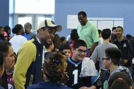 Notre Dame football wide receiver Corey Robinson and his father, former San Antonio Spurs player David Robinson, in background, converse with students at IDEA Carver on Saturday, Jan. 16, 2016, where they and college student athletes encouraged students and distributed T-shirts with logos of various universities through the One Shirt, One Body initiative. The One Shirt, One Body program was created by Corey Robinson and Andrew Helmin, a former Notre Dame track and field athlete, to unite student athletes and schools by donating excess college gear where there is a need. Over 1,000 university tees were given at four San Antonio area IDEA Public Schools.
