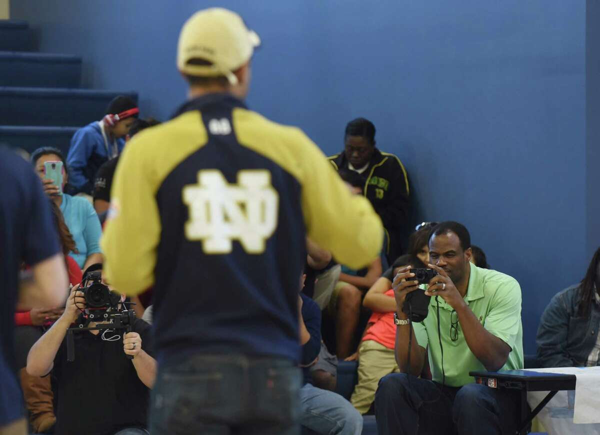 Former San Antonio Spurs player David Robinson photographs his son, Notre Dame football wide receiver Corey Robinson, who speaks to students at IDEA Carver on Saturday, Jan. 16, 2016, where he and other college student athletes distributed T-shirts with logos of various universities through the One Shirt, One Body initiative. The One Shirt, One Body program was created by Corey Robinson and Andrew Helmin, a former Notre Dame track and field athlete, to unite student athletes and schools by donating excess college gear where there is a need. Over 1,000 university tees were given at four San Antonio area IDEA Public Schools.