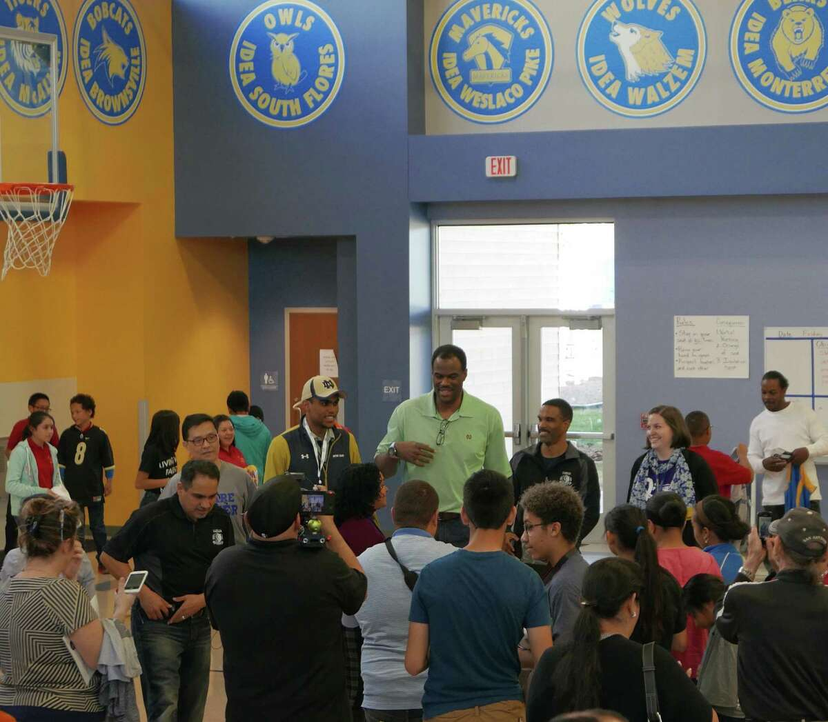 Notre Dame football wide receiver Corey Robinson, wearing baseball cap, and his father, former San Antonio Spurs player David Robinson, middle, converse with students at IDEA Carver on Saturday, Jan. 16, 2016, where they and college student athletes encouraged students and distributed T-shirts with logos of various universities through the One Shirt, One Body initiative. The One Shirt, One Body program was created by Corey Robinson and Andrew Helmin, a former Notre Dame track and field athlete, to unite student athletes and schools by donating excess college gear where there is a need. Over 1,000 university tees were given at four San Antonio area IDEA Public Schools.