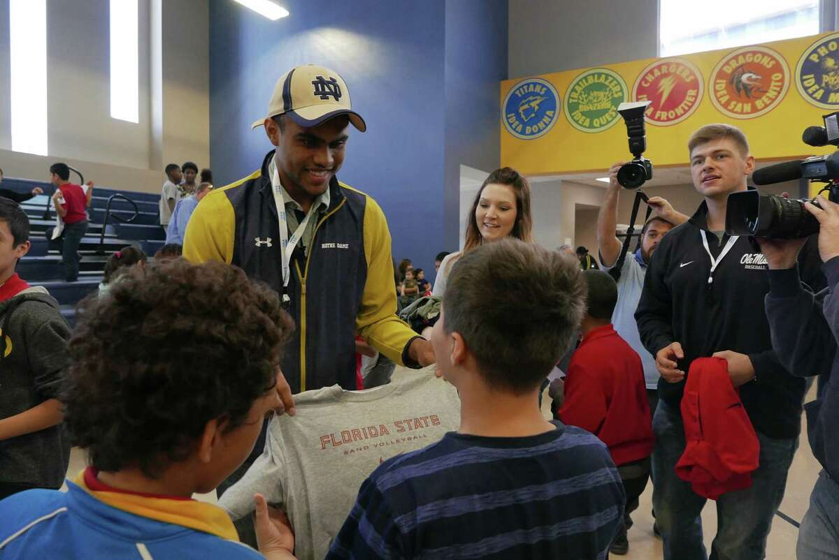 Notre Dame football wide receiver Corey Robinson gives away T-shirts at IDEA Carver on Saturday, Jan. 16, 2016. He and other student athletes encouraged students and distributed T-shirts with logos of various universities through the One Shirt, One Body initiative. The One Shirt, One Body program was created by Robinson and Andrew Helmin, a former Notre Dame track and field athlete, to unite student athletes and schools by donating excess college gear where there is a need. Over 1,000 university tees were given at four San Antonio area IDEA Public Schools.