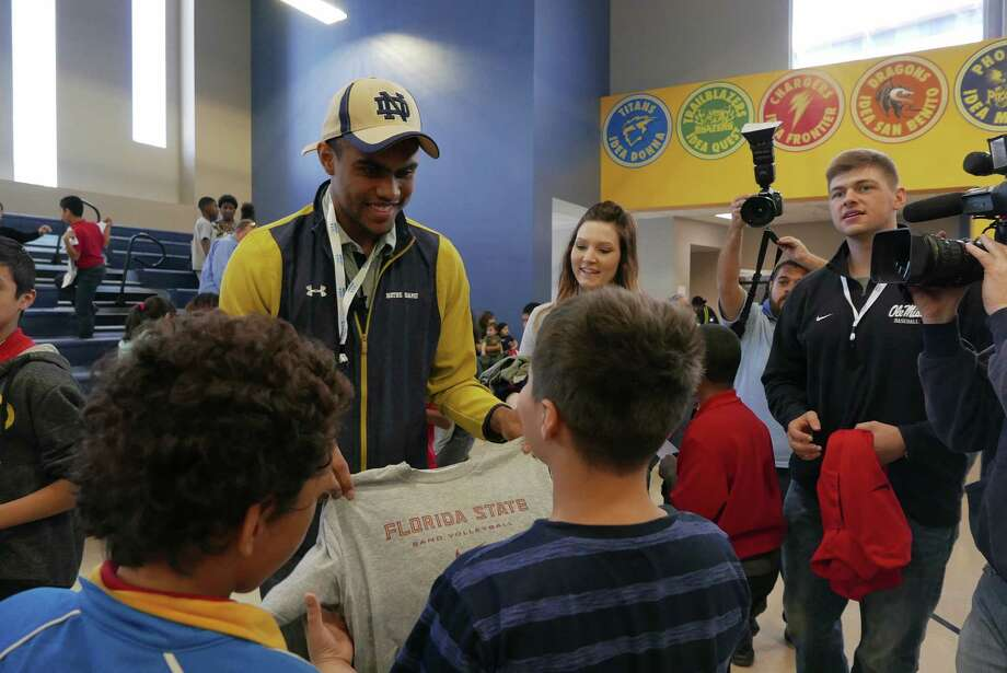 Notre Dame football wide receiver Corey Robinson gives away T-shirts at IDEA Carver on Saturday, Jan. 16, 2016. He and other student athletes encouraged students and distributed T-shirts with logos of various universities through the One Shirt, One Body initiative. The One Shirt, One Body program was created by Robinson and Andrew Helmin, a former Notre Dame track and field athlete, to unite student athletes and schools by donating excess college gear where there is a need.  Over 1,000 university tees were given at four San Antonio area IDEA Public Schools. Photo: Billy Calzada, San Antonio Express-News / San Antonio Express-News