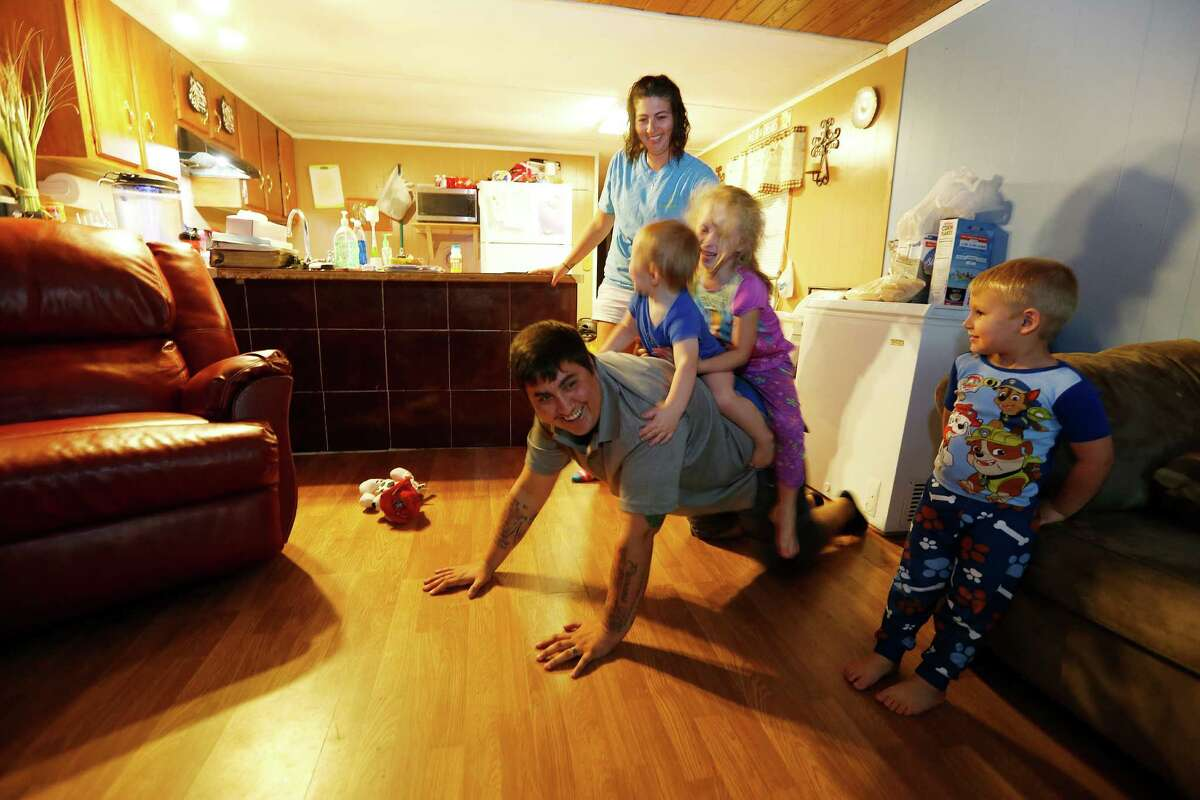 """Peyton Orgeron, who recently transitioned from female to male, enjoys time at home with his wife, Elizabeth, and children, from left, Eastin, Halena and Brendley. Peyton was glad when he told a co-worker about his transition and heard in reply: """"Do what you need to be happy."""""""
