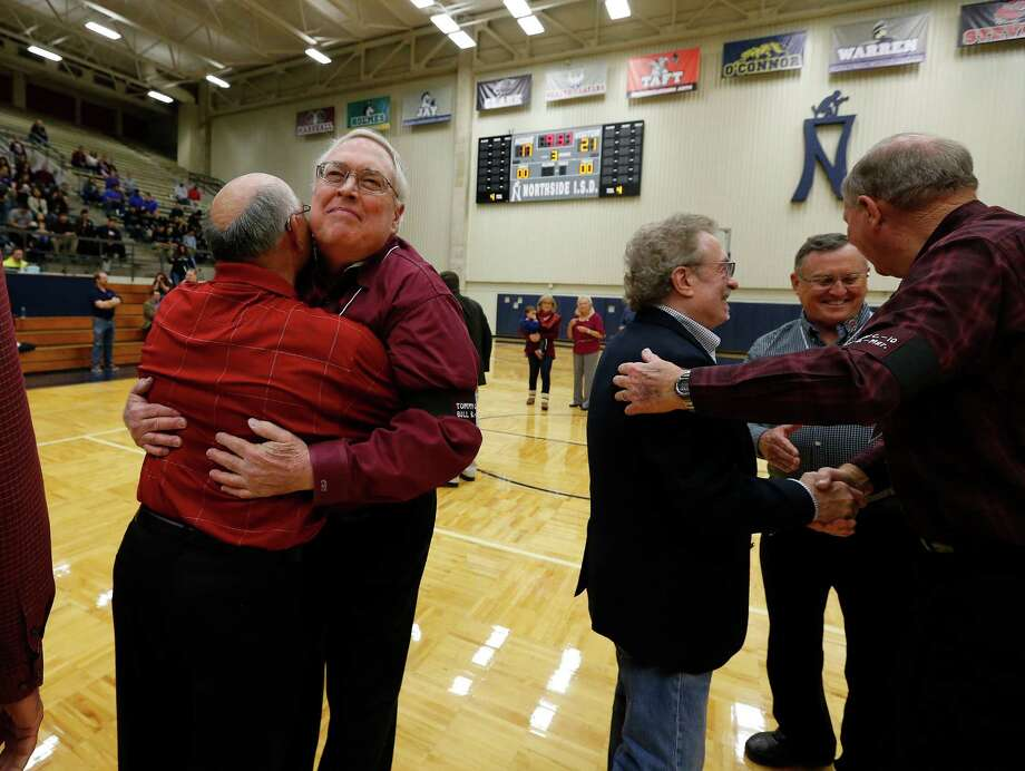 Former Marshall High School basketball players Carl Steinle (second from left) and Johnny Pedroza offer hugs to one another as their former coach Ted Dockery (far right) shakes hands with other former players Greg Hahn (third from right) and Terrell Lillard as  Northside ISD honors members of the 1966 John Marshall High School basketball team during halftime of the boys' game between Marshall and Clark at Paul Taylor Fieldhouse on Saturday, Jan. 16, 2016. 14 of the players including head coach Ted Dockery were honored for their accomplishment of winning the '66 State 3A Championship in basketball. (Kin Man Hui/San Antonio Express-News) Photo: Kin Man Hui, Staff / San Antonio Express-News / ©2016 San Antonio Express-News
