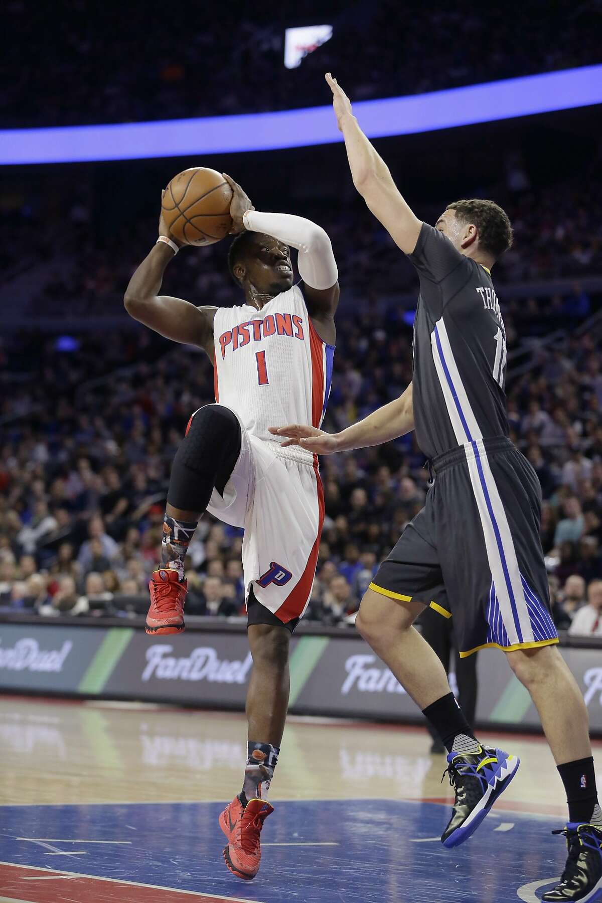 Detroit Pistons guard Reggie Jackson (1) shoots over Golden State Warriors guard Klay Thompson (11) during the first half of an NBA basketball game, Saturday, Jan. 16, 2016, in Auburn Hills, Mich. (AP Photo/Carlos Osorio)