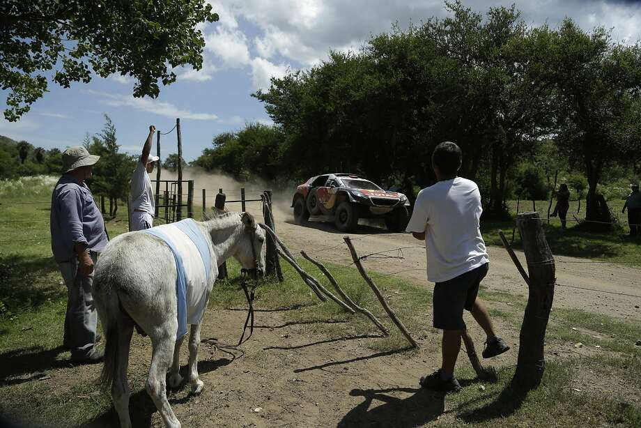 Farmers with a donkey with an Argentine flag draped over, look as Peugeot driver France's Cyril Despres and co-driver David Castera, race by the farm's entrance during the twelfth stage of the 2016 Dakar Rally, between San Juan and Villa Carlos Paz, Argentina, Friday, Jan. 15, 2016. (AP Photo/Jorge Saenz) Photo: Jorge Saenz, Associated Press