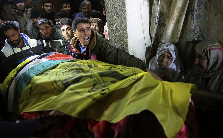 Palestinian relatives mourn while carrying the covered body of Mohammed Qeta, 26, during his funeral at his family house in Khan Younis, Gaza Strip, Saturday, Jan. 16, 2016. Palestinian Health Ministry spokesman Ashraf al-Kidra says, Qeta was killed Friday during clashes with Israeli soldiers on the Israeli border with the east of Bureij refugee camp. Photo: Adel Hana, Associated Press