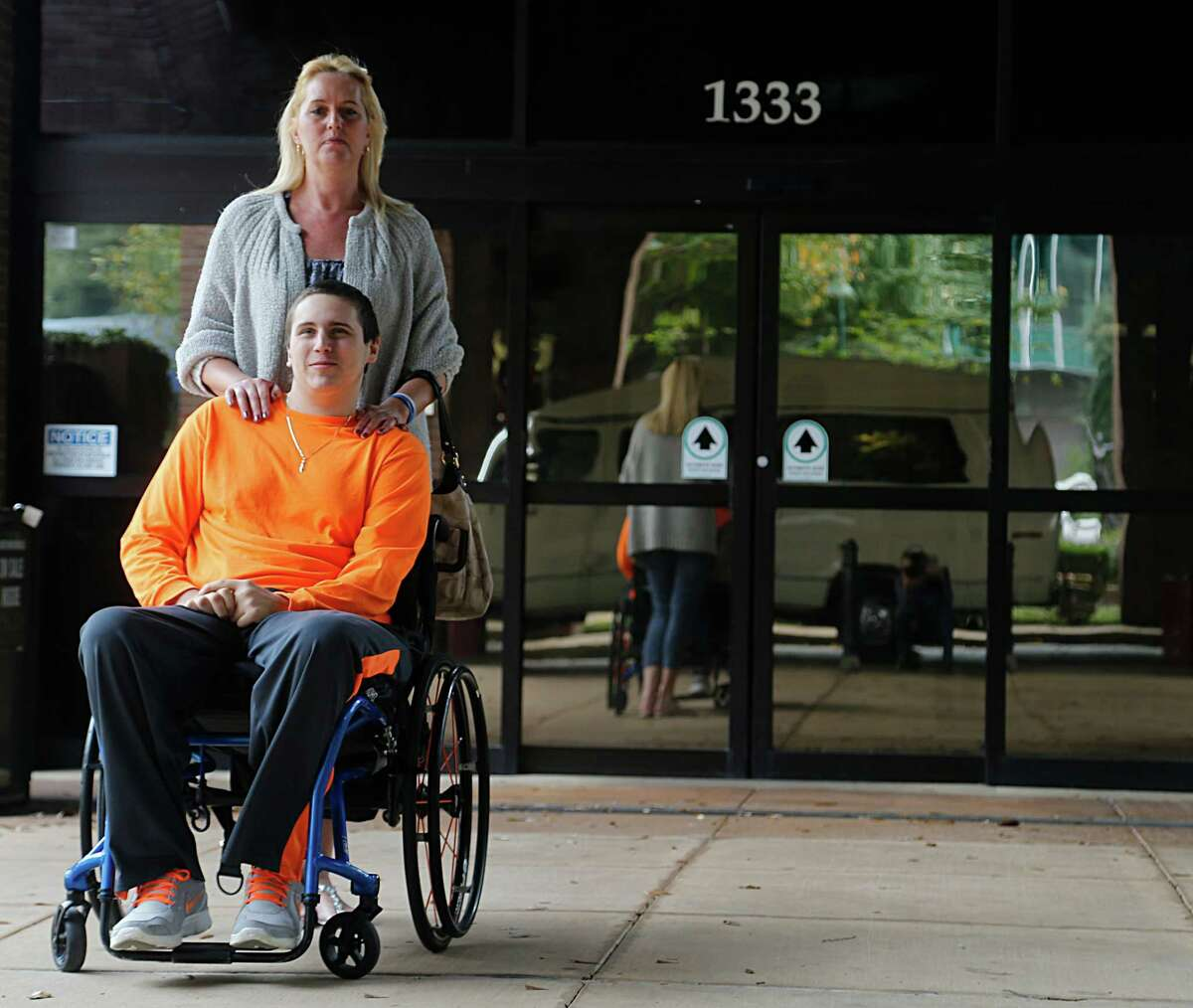 Louis Tontodonato, 20, who broke his neck in a car accident a year ago and his mother Kelly Tontodonato wait outside TIRR Memorial Hermann after test Wednesday, Dec. 16, 2015, in Houston.