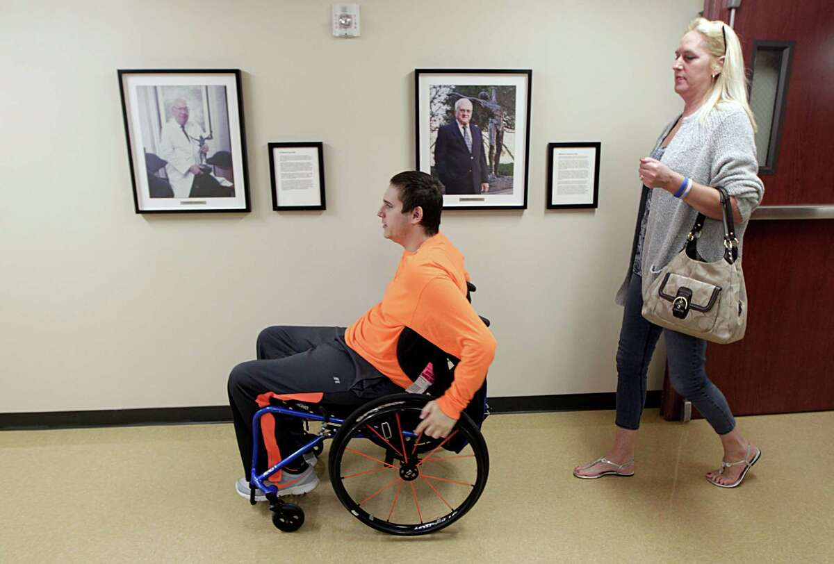 Louis Tontodonato left, 20, who broke his neck in a car accident a year ago leaves TIRR Memorial Hermann after test with his mother Kelly Tontodonato Wednesday, Dec. 16, 2015, in Houston.