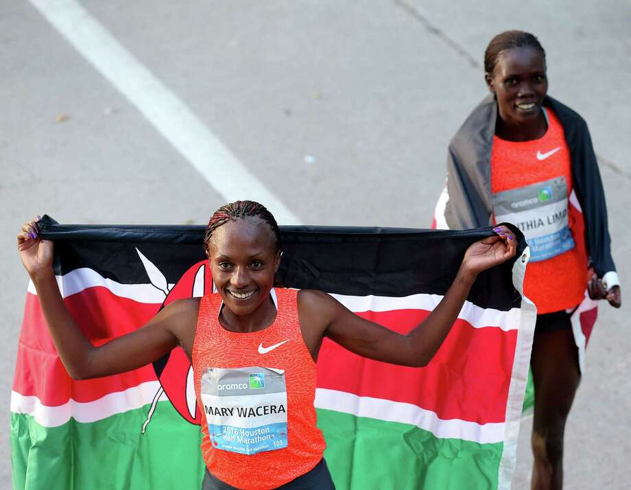 Mary Wacera  poses with a Kenyan flag after beating Cynthia Limo in the  the half marathon with a course record during the Houston Marathon on Sunday, Jan. 17, 2016, in Houston. Photo: Elizabeth Conley, Houston Chronicle / © 2016 Houston Chronicle