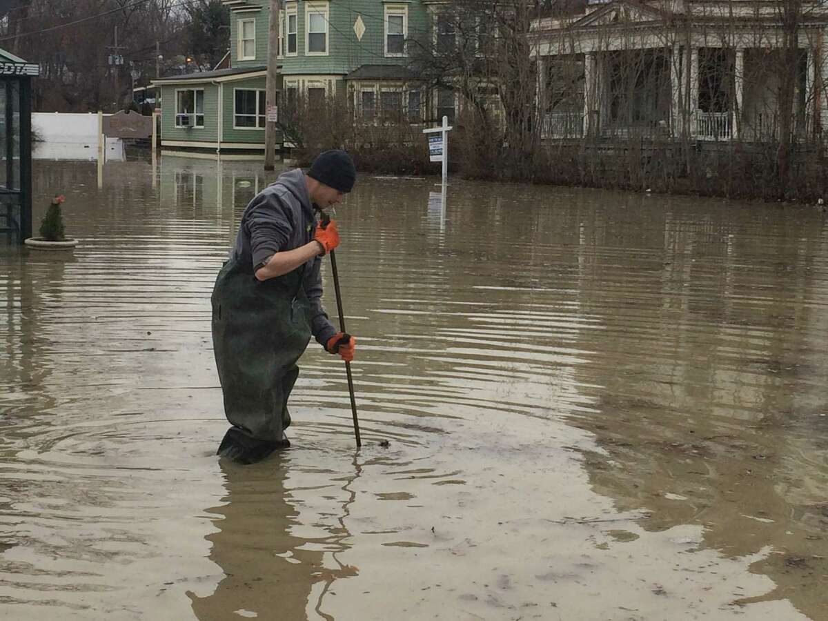 A worker with the City of Troy public works department tries to open a manhole cover during flooding on Second Avenue Sunday, Jan. 17. 2016. (Lauren Stanforth)