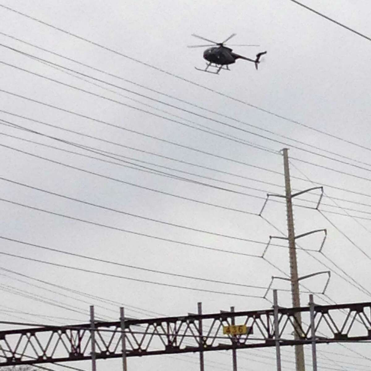 A helicopter is seen hovering low over train tracks in Darien on Sunday, January 17, 2015.