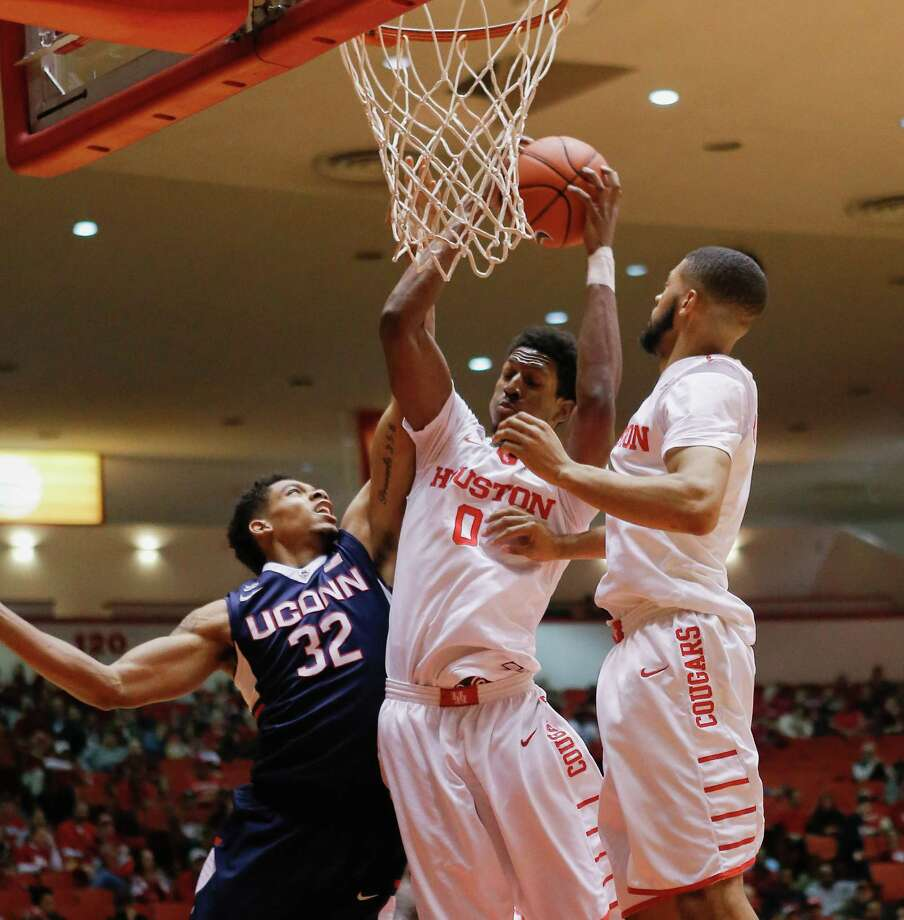 Houston forward Danrad Knowles (0) grabs a rebound away from Connecticut forward Shonn Miller (32) as guard LeRon Barnes (4) watches during the first half of an NCAA college basketball game Sunday, Jan. 17, 2016, in Houston. (AP Photo/Bob Levey) Photo: Bob Levey, Associated Press / FR156786 AP