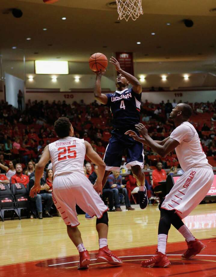Connecticut guard Sterling Gibbs (4) shoots over Houston guard Galen Robinson Jr. (25) and Devonta Pollard, right, during the first half of an NCAA college basketball game Sunday, Jan. 17, 2016, in Houston. (AP Photo/Bob Levey) Photo: Bob Levey, Associated Press / FR156786 AP