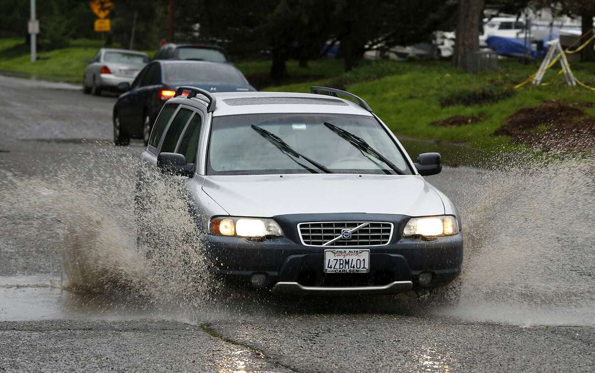 A car splashes water as it drives through a large puddle near Cesar Chavez Park in Berkeley, California, on Sunday, Jan. 17, 2016.