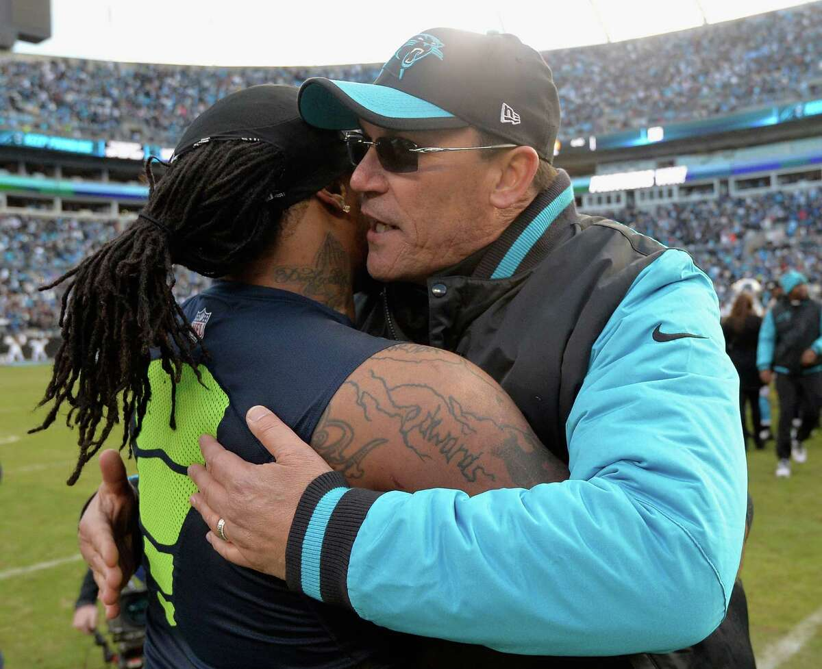 CHARLOTTE, NC - JANUARY 17: Head coach Ron Rivera of the Carolina Panthers hugs Marshawn Lynch #24 of the Seattle Seahawks. The Carolina Panthers defeated the Seattle Seahawks 31-24 at the NFC Divisional Playoff Game at Bank of America Stadium on January 17, 2016 in Charlotte, North Carolina.